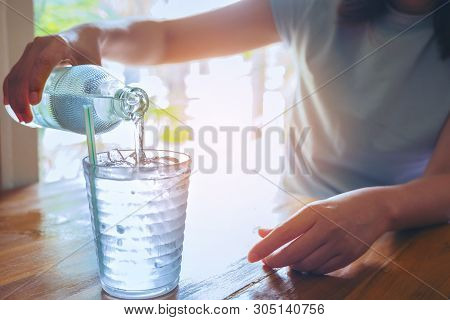 Hand Women Holding The Glass Bottle Of Water Cool And Pouring Water Into The Glass On The Vintage Wo