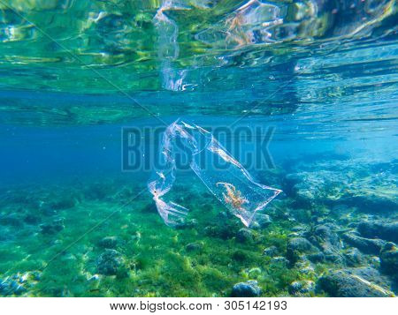Plastic Bag With Seaweed Inside In Blue Sea Water, Underwater Photo. Tropical Sea With Plastic Trash