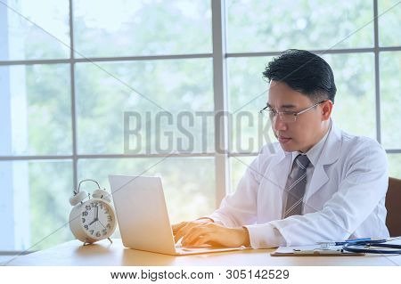 Doctor With Stethoscope Working Writing On Paperwork With Clipboard And Laptop Computer On Table In