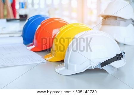 Red Yellow White And Blue Safety Hard Hat On The Blueprint With Contract Folder As Background. Engin