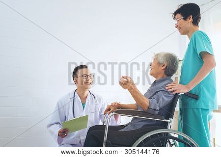 Doctor Holding Elderly Patient 's Hand In A Wheelchai, Giving Support To His Elderly Patient.