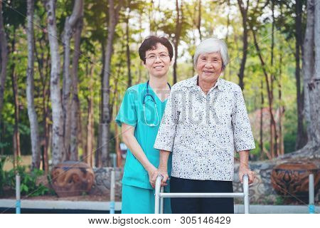 Smiling Caregiver Senior Nurse Take Care A Senior Patient In Walker For Relaxing And Looking Around