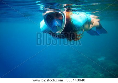 Woman Swimming In Blue Sea. Girl Snorkeling In Full-face Mask. Snorkel Closeup Underwater Photo. Sno