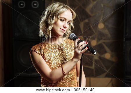 Portrait Of Young Blonde Woman With Microphone On Dark Background.