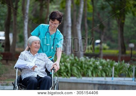 Smiling Caregiver Senior Nurse Take Care A Senior Patient On Wheelchair For Relaxing And Looking Aro