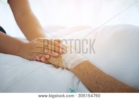 Medical Doctor Holing Senior Patient's Hands And Comforting Her, Hand Of Man Touching Senior Woman I