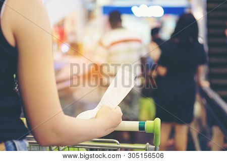 Blurry Of Hand Of Woman Asia Hold A Bill And A Long Receipt Of Supermarket/mall For Background And S