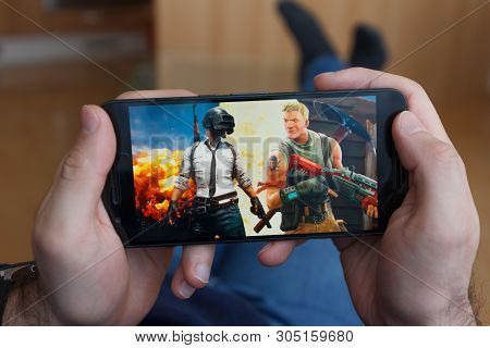 Los Angeles, California - June 3, 2019: Lying Man Holding A Smartphone And Compares Pubg And Fortnit
