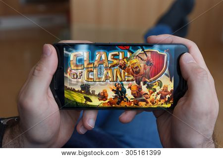 Los Angeles, California - June 3, 2019: Lying Man Holding A Smartphone And Compares Clash Of Clans A