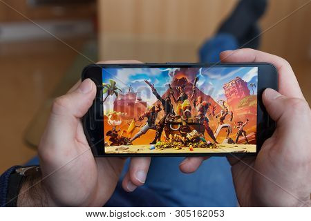 Los Angeles, California - June 3, 2019: Lying Man Holding A Smartphone And Playing The Fortnite Game