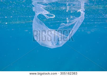Plastic Bag In Blue Sea. Garbage In Sea Underwater Photo. Blue Sea Water With Plastic Trash. Ecology