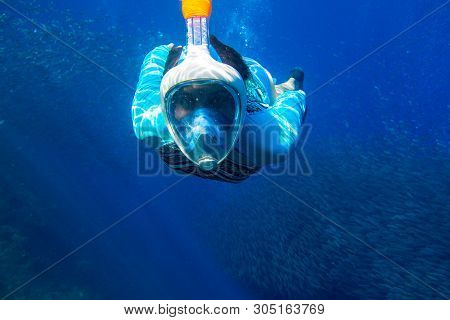 Woman Swimming In Blue Sea. Girl Snorkeling In Full-face Mask. Snorkel With Fish School Underwater P