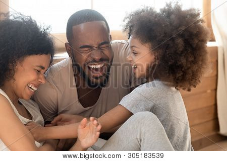 Happy African Family With Kid Daughter Tickling Laughing Together