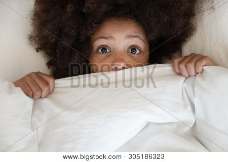 Scared African Kid Looking At Camera Covering Blanket In Bed