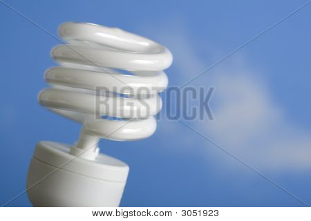 An energy-saving compact fluorescent light bulb against a blue sky. poster