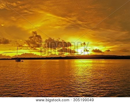 A Picturesque Inspirational Brightly Coloured Gold And Orange Cloudy Cumulus Tropical Sunrise Seasca