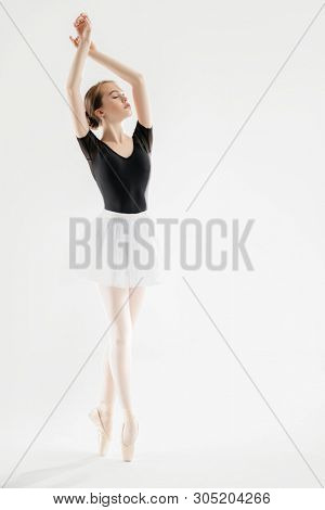 A full length portrait of an elegant refined ballet female dancer posing in the studio over the white background. Talent, fashion for ballet dancers.