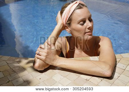 Portrait of stunning woman relaxing in luxurious pool poster