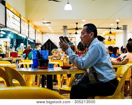 Singapore - 17 Mar 2019 - A Middle Aged Man In Office Attire Enjoys A Late Night Beer At An Eatery /