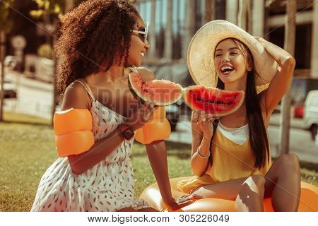 Contended Girlfriends Talking And Holding Watermelon Pieces In Hands