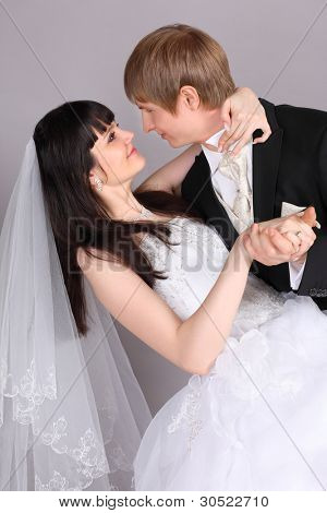 Groom and beautiful bride dance in studio on gray background; close up