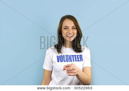 Happy volunteer girl pointing at you on blue background