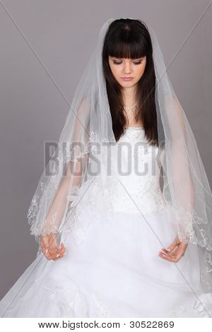 Beautiful melancholy bride dressed in white dress look down on gray background