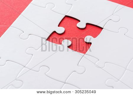 selective focus of white incomplete jigsaw on red poster