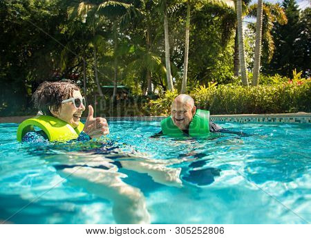 Senior couple splashing, playing, and having fun at a water park. Smiling and having a great vacation enjoying an active retirement.