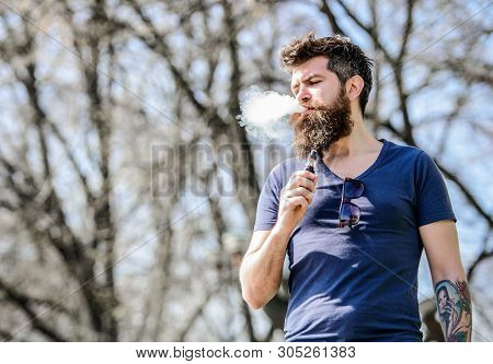 Bearded Brutal Male Smoking Electronic Cigarette. Hipster Man Hold Vaping Device. Health Safety And