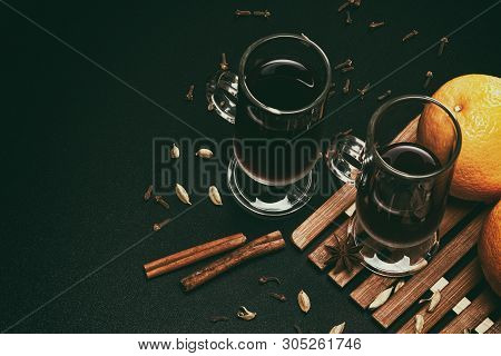 Mulled Wine With Spices And Oranges On Black Table Background. Retro Still Life With Copy Space