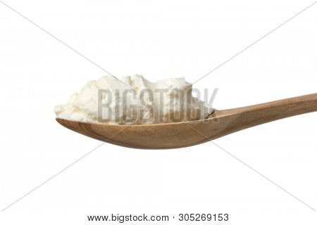 Fresh white cheese, called fromage blanc in France at a wooden spoon on white background