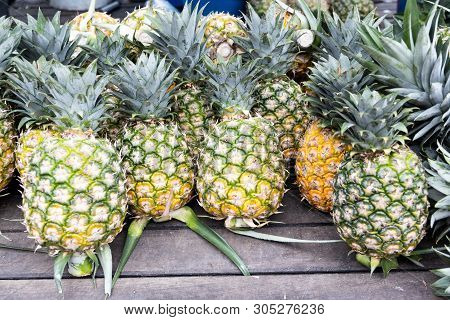 Heap Of Freshly Harvested Organic Pineapple On Wooden Surface