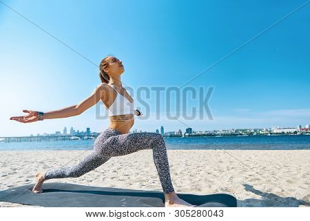 Outdoors Portrait Of Young Slim Athletic Woman Standing In Yoga Asana With Arms Apart On The City An