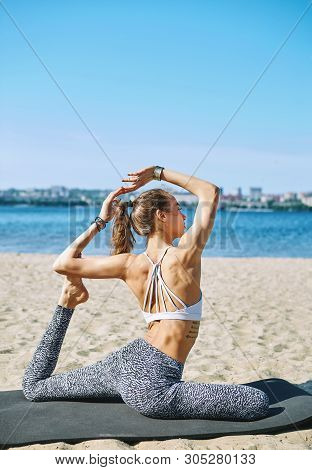 Young Slim Athletic Woman Makes Yoga Exercises And Stretching On The Sand Beach With City Background