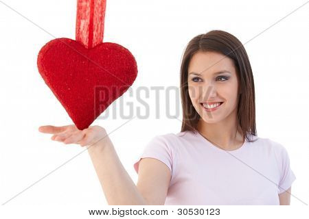 Smiling woman in love, balancing a red heart on palm.?