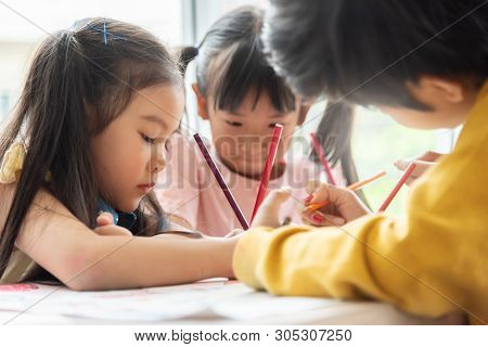 Asian Little Kids Are Colouring In A Classroom At A School.