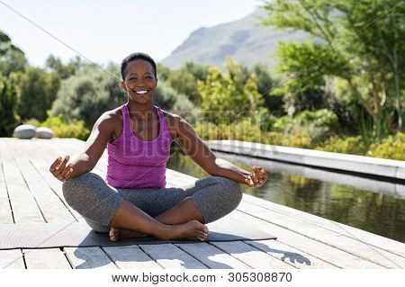 Portrait of smiling woman in lotus position near swimming pool looking at camera. Healthy black mature woman meditating and sitting in lotus pose on yoga mat. Happy lady in zen pose doing meditation.