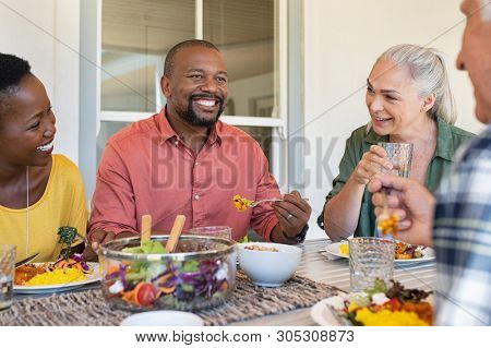 Happy smiling friends enjoying lunch together at home. Mature multiethnic people celebrating happy occasion while eating healthy food. Group of senior couple and african couple talking during meal.