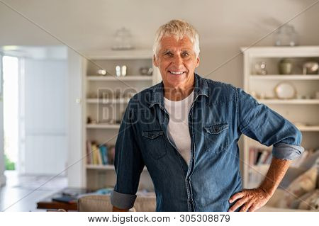 Happy senior man standing in living room and looking at camera. Portrait of cheerful old man with blue denim shirt at home relaxing. Satisfied man enjoying the retirement at home.