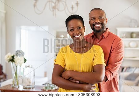 poster of Smiling mature couple holding each other at home. Loving african couple standing in living room embracing and looking at camera. Husband hugging wife from stomach at new apartment with copy space.