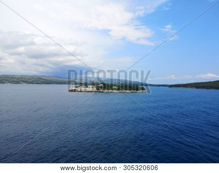 little islad Mrduja with lighthouse in front of town Milna on island Brac, Croatia