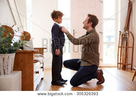 Single Father At Home Getting Son Wearing Uniform Ready For First Day Of School