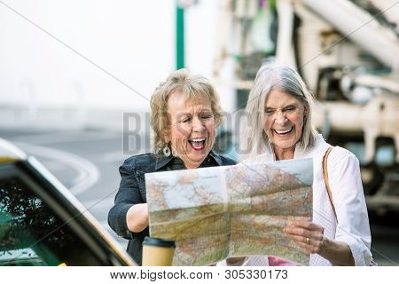 Two Laughing Women In A City Center Checking Road Map