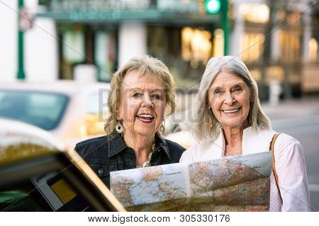Two Women In A City Center Sharing A Road Map