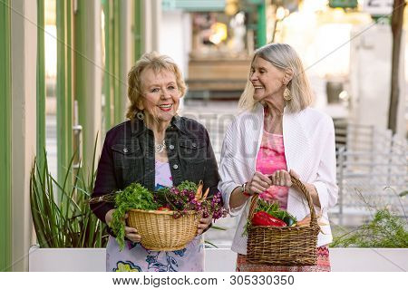 Two Senior Women Returning With Baskets Of Produce From Farmers Market
