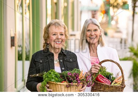 Smiling Senior Women Returning With Produce From Farmers Market