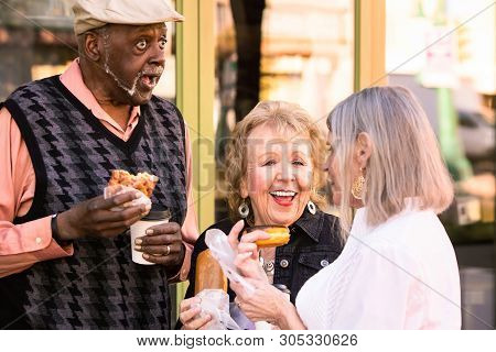 Three Seniors Eating Donuts And Laughing On A Downtown Street