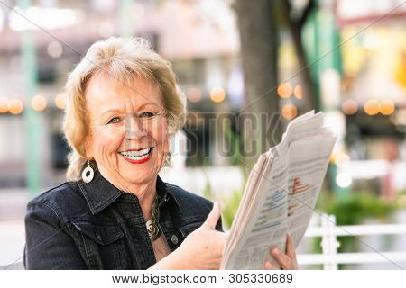 Happy Woman Downtown With Newspaper Reacting To Story