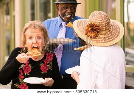 Three Seniors Eating Slices Of Pizza Downtown